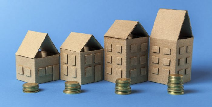 Real estate and money. Cardboard houses and coins on a blue background. Growth in rental prices. Investing in building.